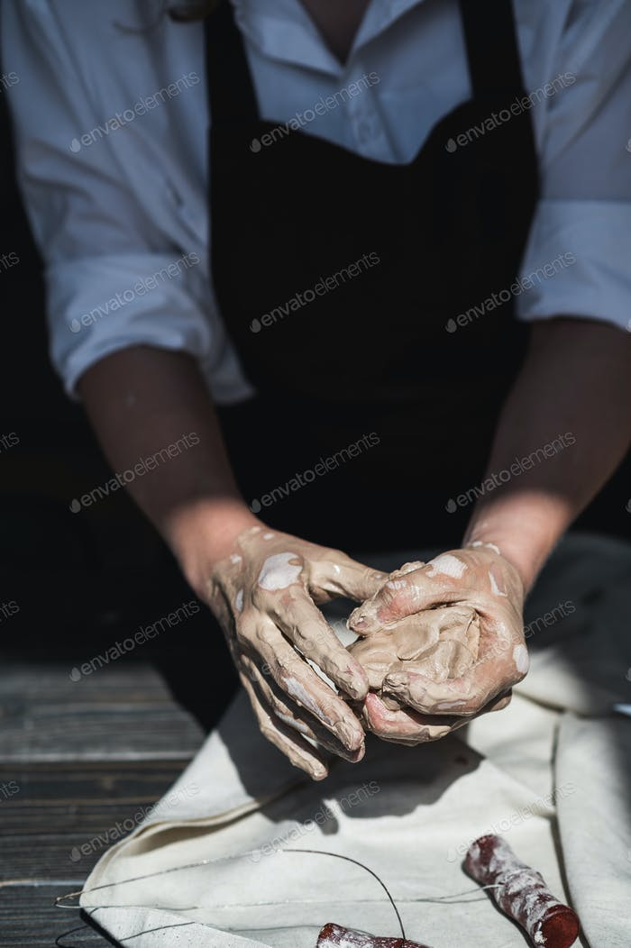 The potter's woman hands are shaping a cup from a clay. The process of creating pottery. The