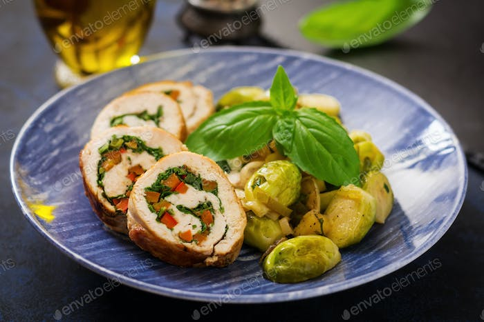 Chicken rolls with greens, garnished with stewed Brussels sprouts, apples and leeks on a blue plate.