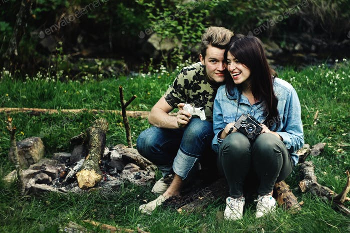 stylish beautiful couple camping smiling,  with analog photo camera in spring sunny mountains