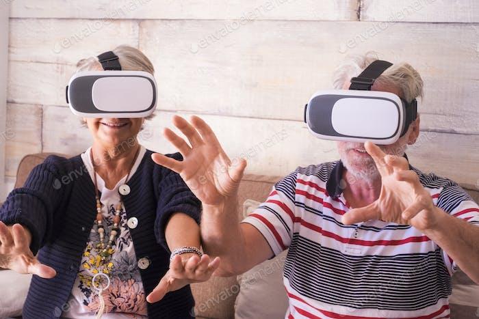 Hände zum Schutz, während ein kaukasischer Mann und eine Frau im Alter von 70 Jahren zu Hause mit Technologie spielen