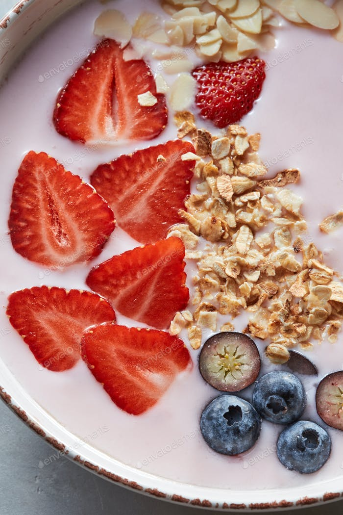 Homemade granola in a plate, sliced strawberries, yogurt, almonds, blueberries - ingredients for