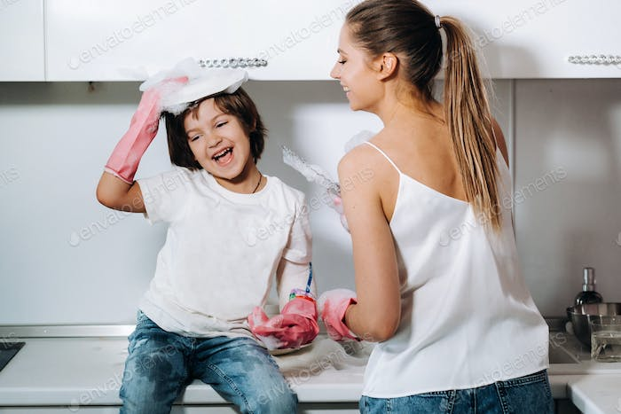 housewife mom in pink gloves washes dishes with her son by hand in the sink with detergent. A girl