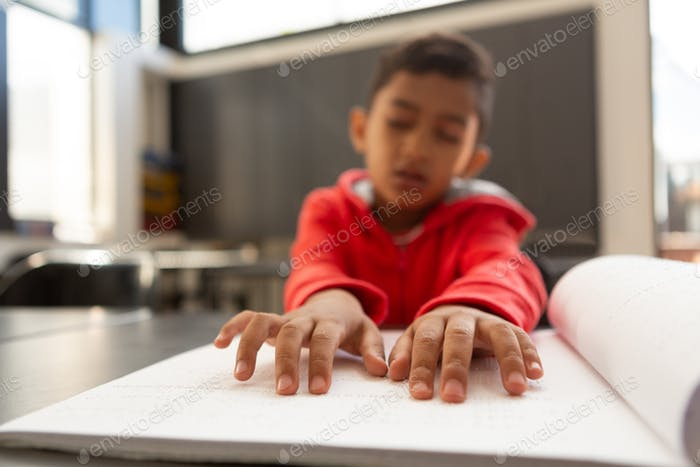 Schoolboy hands reading a braille book at desk in a classroom at elementary school