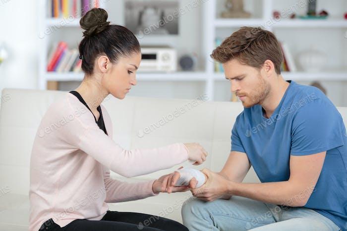 sanfte Frau hilft ihrem verletzten Freund