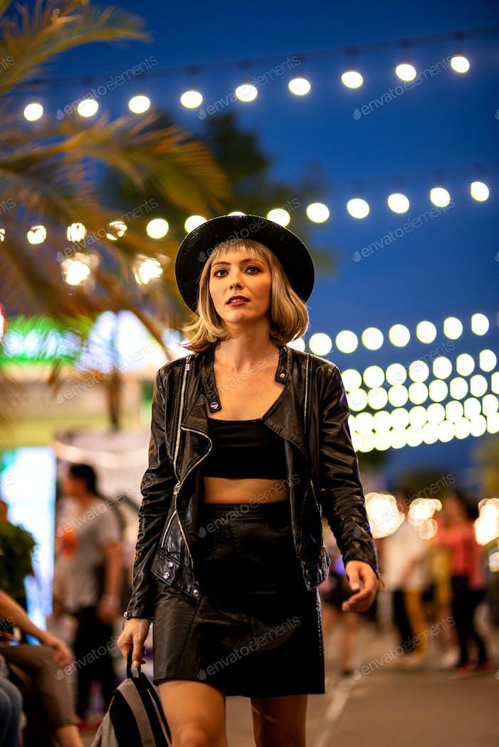 Cheer day and night. Beautiful female tourist exploring night city alone.