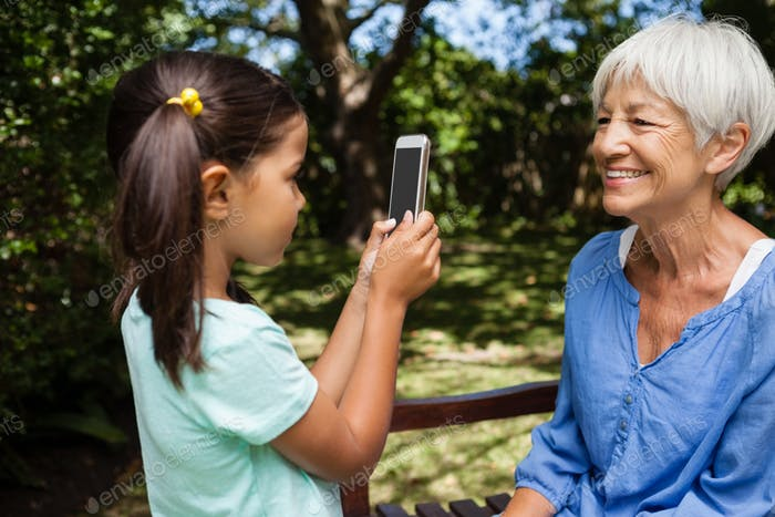 Side view of girl taking photograph of grandmother sitting on bench