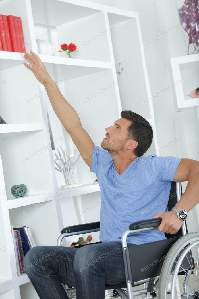 disabled man selecting a book from bookshelf