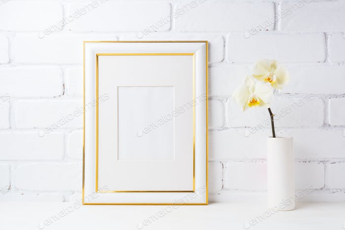 Gold decorated frame mockup with soft yellow orchid in vase