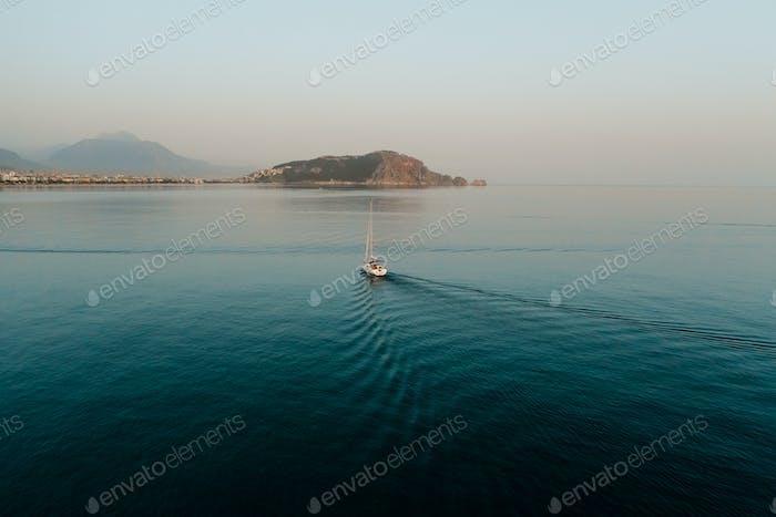 Luftaufnahme der Yacht auf dem Meer in Bewegung zum felsigen Berg