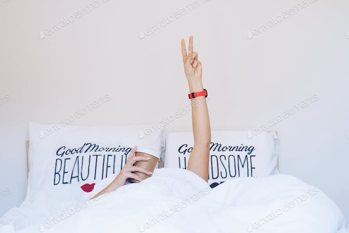Woman's hands showing the v-sign and holding cup under blanket o