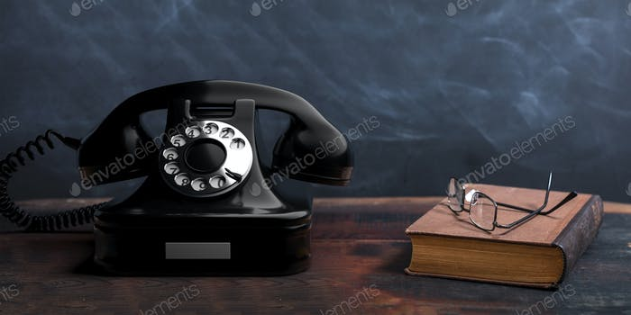 Telephone, black color, old books and reading glasses on a wooden table, black board background.