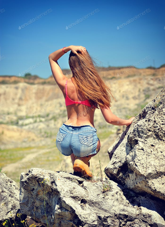 Sexy woman on the stone, rear view of young beautiful girl