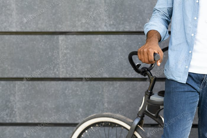 Unrecognizable black man standing near bicycle against grey wall background
