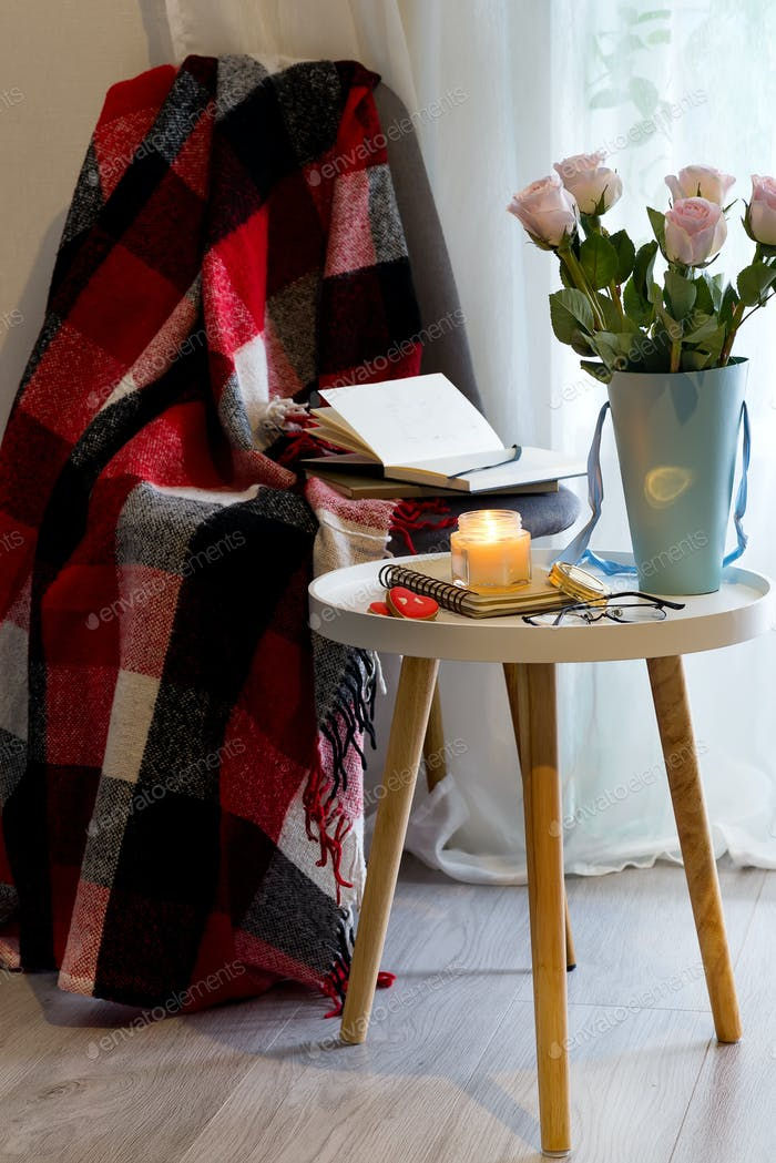 A candle with a notebook on a table with pink roses in a box near a window with a book, a plaid and