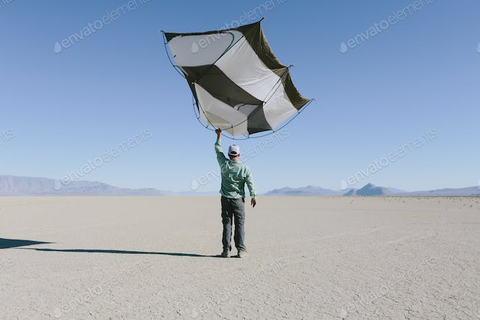 Man holding a capsule pod camping tent above his head in the open space of the desert.