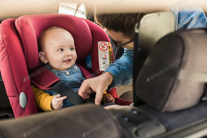 Father fasten his baby in car seat