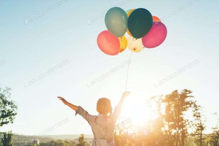 Girl holding balloons in one hand looking to sky