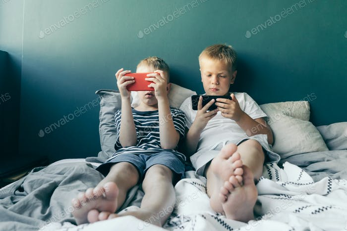 Two schoolboys are sitting on the bed and playing on the phone. Generation Z