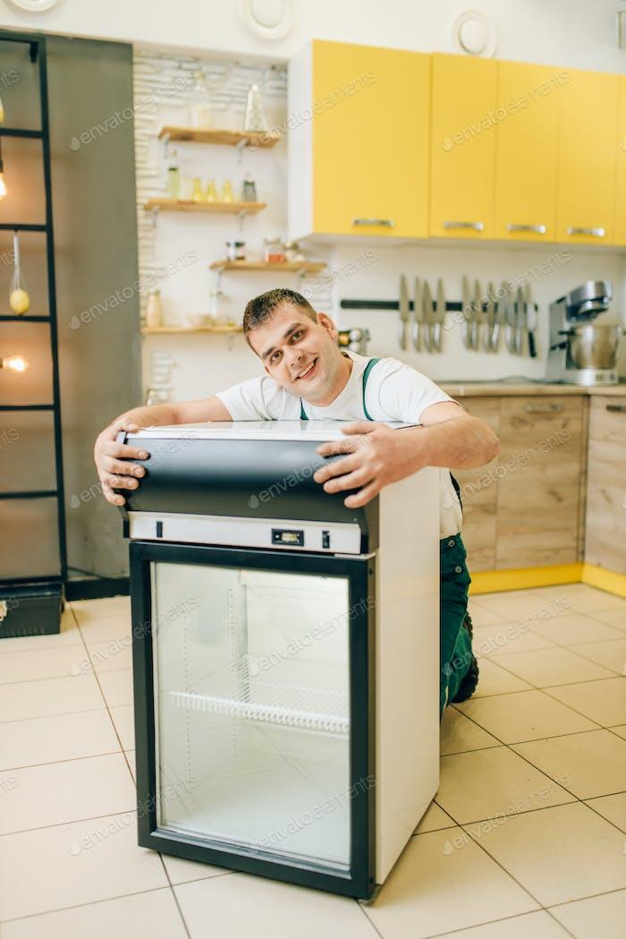 Worker in uniform hugs refrigerator at home