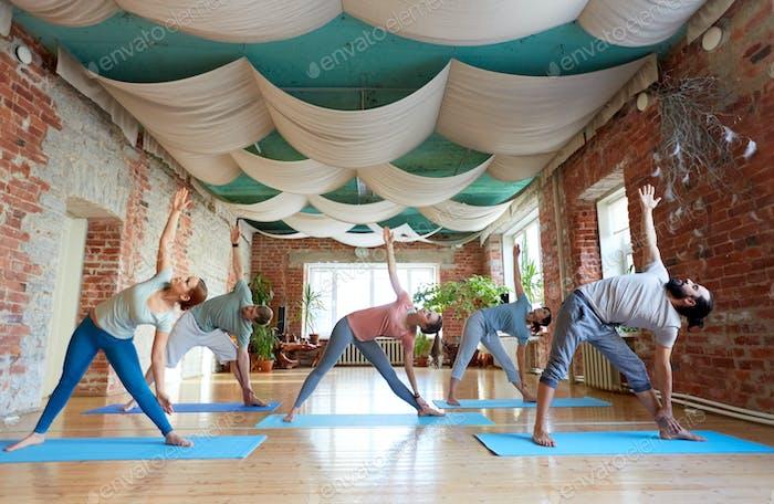 Gruppe von Menschen tun Yoga Dreieck Pose im Studio