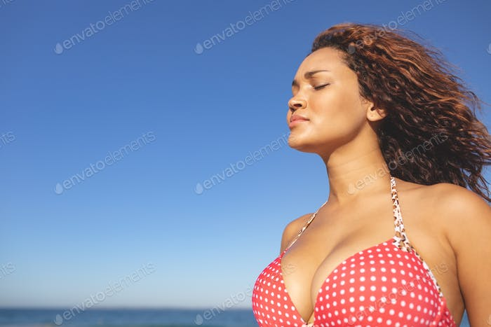 Side view of beautiful mixed race woman in bikini standing with eyes closed on the beach