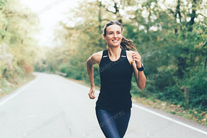 Young caucasian athletic brunette woman in sportswear runs a marathon on the road through the forest