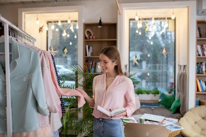 Fashion designer examining material of the pink coat