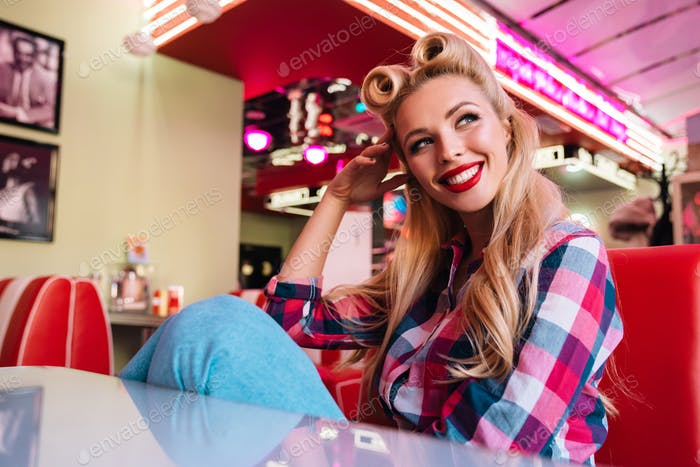Photo of happy seductive woman smiling while sitting