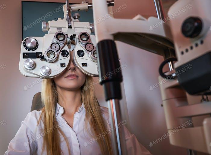 Frau überprüft ihren Anblick im Optikerkabinett