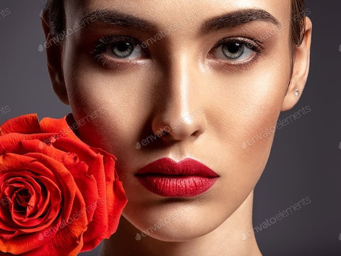 Beautiful young fashion woman with red lipstick. Pretty model with flower.