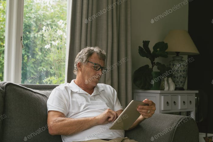 Active senior Caucasian man sitting on sofa and using digital tablet in living room