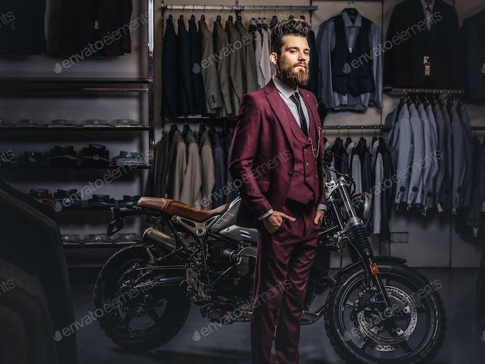 Татуированный бородатый мужчина позирует рядом с ретро спортивный мотоцикл в магазине мужской одежды