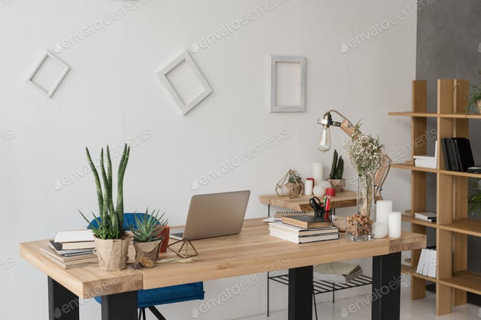 офисный стол с ноутбуком, книгами, свечами и канцелярскими принадлежностями