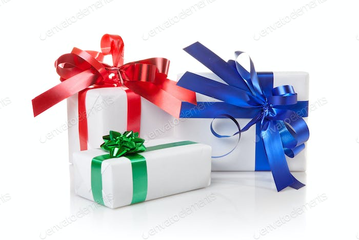 Holiday gifts with color ribbons isolated on white