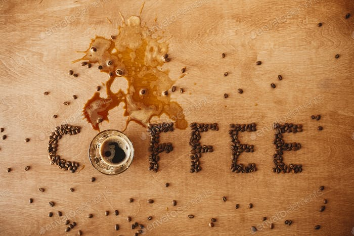 Coffee word made of coffee beans and spilled coffee from glass cup of hot espresso
