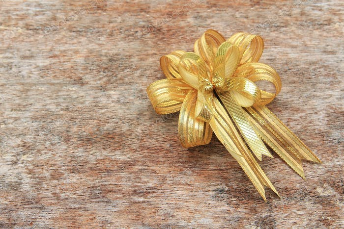 Golden Ribbon on old wood background