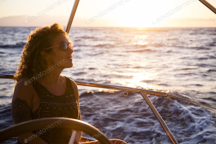 Portrait view of blonde curly long hair woman with tatoo enjoying the trip on a boat