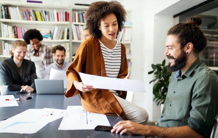 Glückliche junge Geschäftsleute Kollegen sprechen im Büro arbeiten