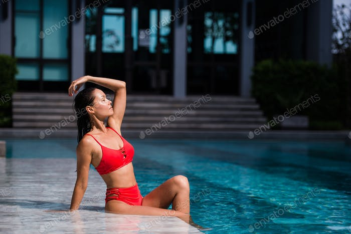 Beautiful dark hair sexy woman young girl model in sunglasses and elegant red sexy swimsuit lingerie