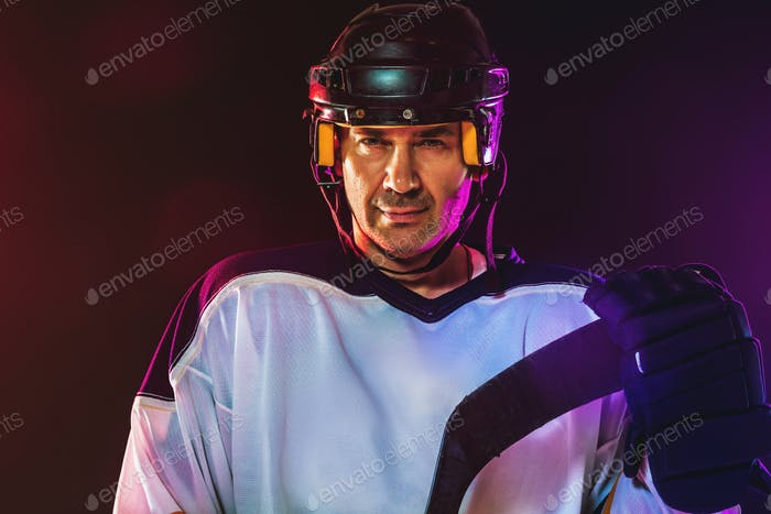 Male hockey player with the stick on ice court and dark neon colored background