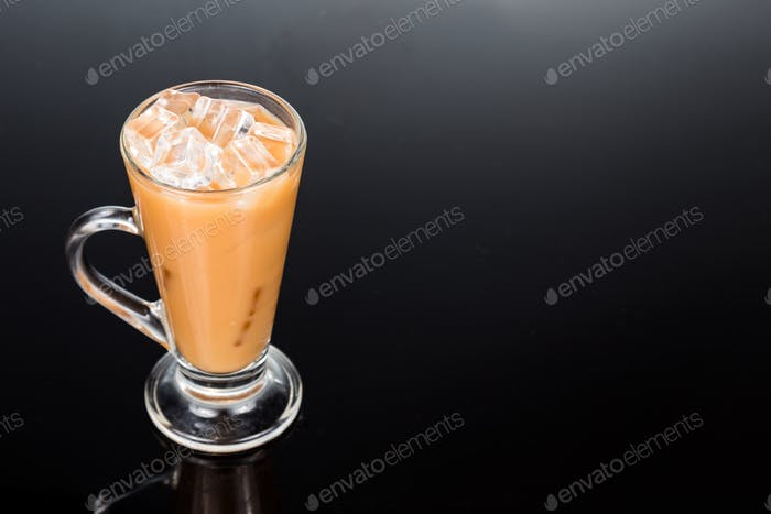 Refreshing ice cold tea with milk in transparent glass on black background