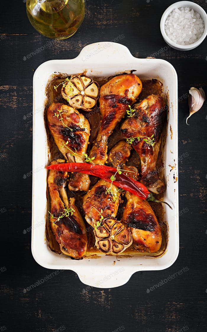 Appetizing oven baked golden chicken drumsticks  in a baking dish on a dark table. Asian cuisine.