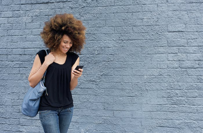 Smiling woman walking and looking at mobile phone