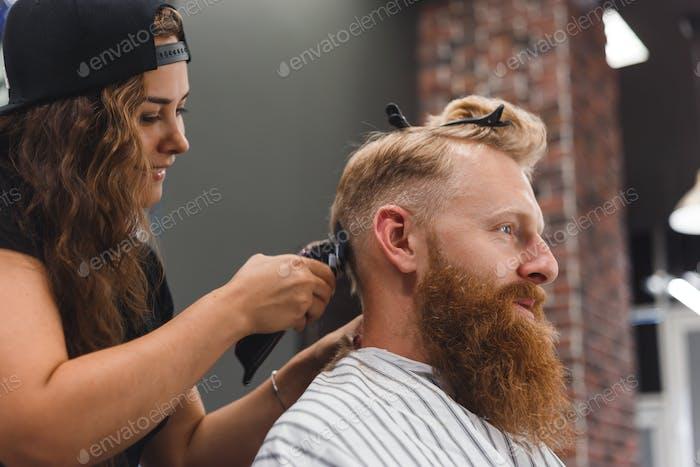 Weibliche Friseur in Maske schneidet ein Mann Haare mit Haarspange. Frisur während der sozialen Distanzierung