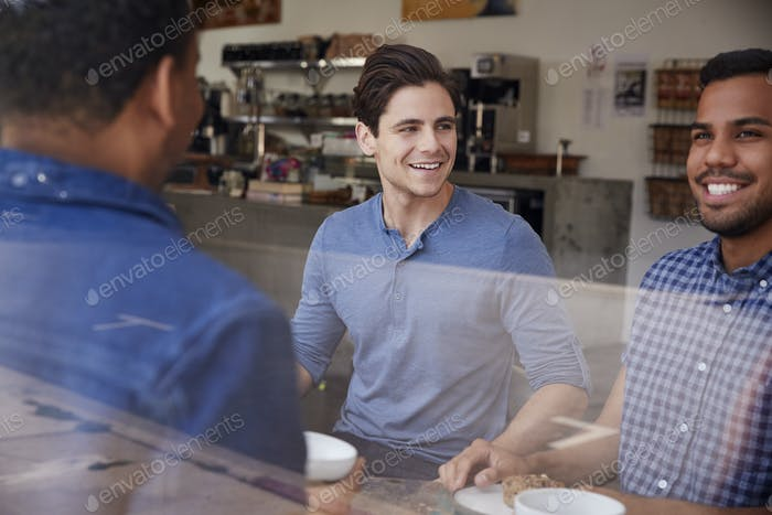 Three male friends having coffee together at a coffee shop