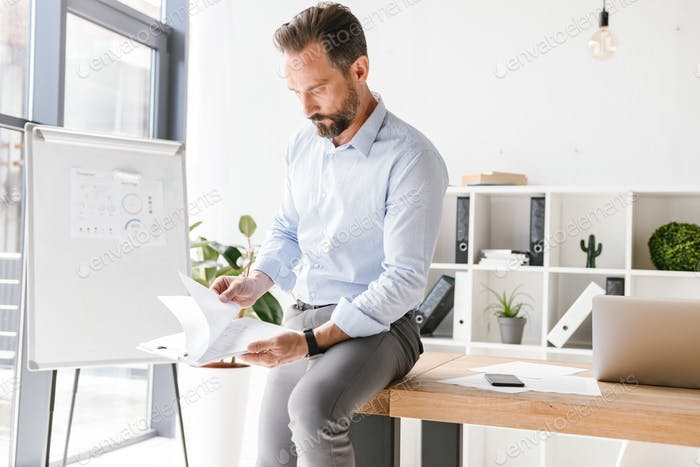 Smiling businessman looking at paperwork