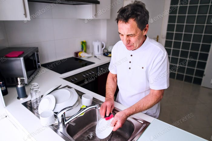 Senior man washing dishes. Domestic kitchen.