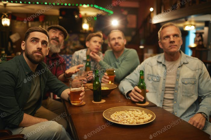 Group of friends drinking beer in sport bar