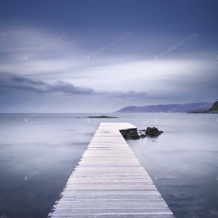 Wooden pier, rocks and sea on misty sunset.