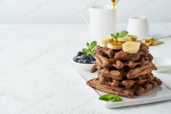 Chocolate banana waffles on white table, copy space, side view. Sweet brunch